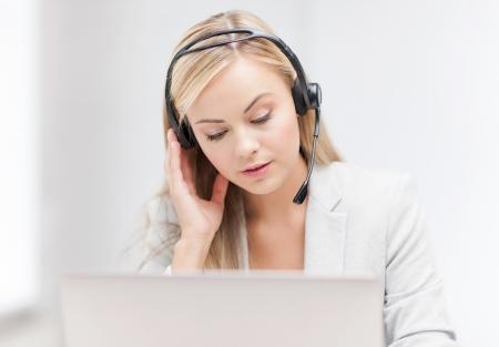 centro de computo: operador de línea telefónica de ayuda femenina con auriculares y un ordenador portátil Foto de archivo