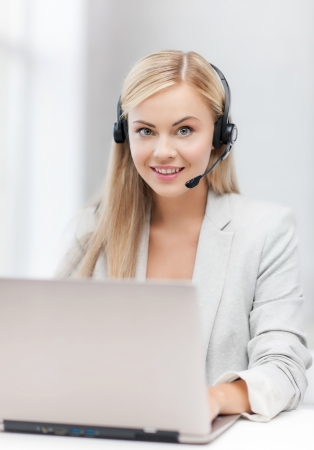 smiling female helpline operator with headphones and laptop Stock Photo - 19504536