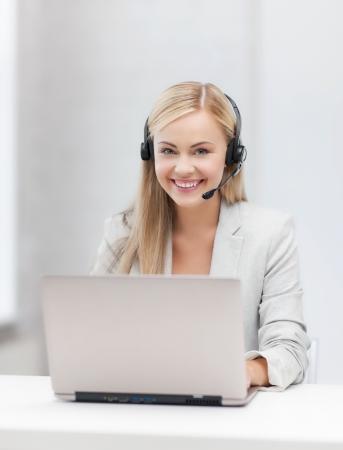 helpline: smiling female helpline operator with headphones and laptop