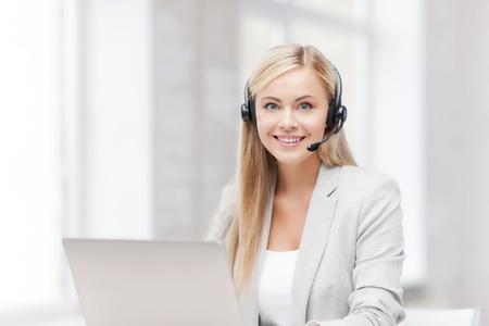 recepcionista: sonriendo operador de l?a telef?a de ayuda femenina con auriculares y un ordenador port?l Foto de archivo