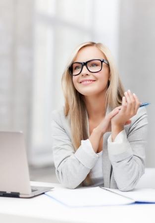 indoor foto van lachende vrouw met notitieboekje en pen Stockfoto