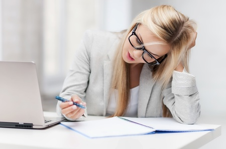 stressful: indoor picture of bored and tired woman taking notes