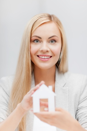 picture of young woman holding white paper house photo