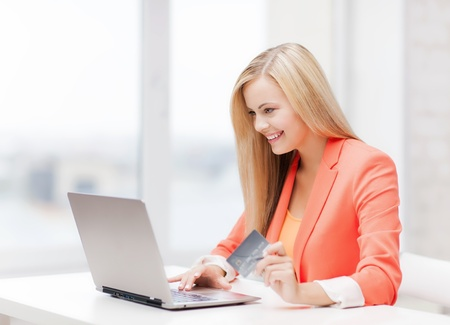 online: smiling businesswoman with laptop and credit card