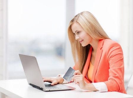 buying online: smiling businesswoman with laptop and credit card