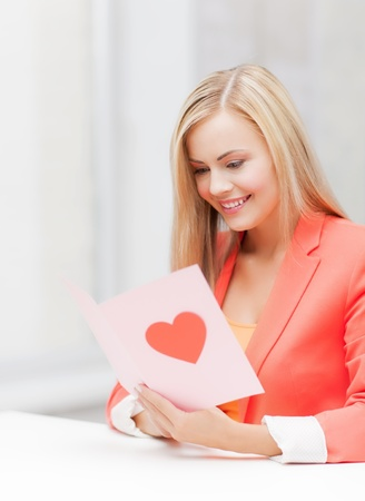 picture of woman holding postcard with heart shape  photo