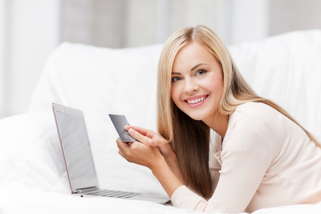 order online: smiling businesswoman with laptop and credit card