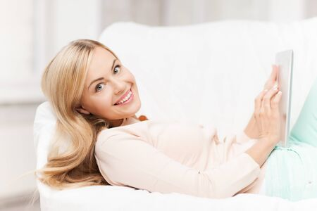 smiling woman lying on the couch with tablet pc photo
