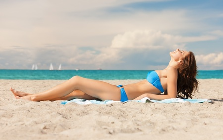 picture of young woman lying on the beach  photo