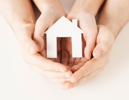 hands holding house: pisture of man and woman hands holding paper house
