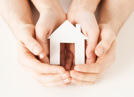 model home: pisture of man and woman hands holding paper house