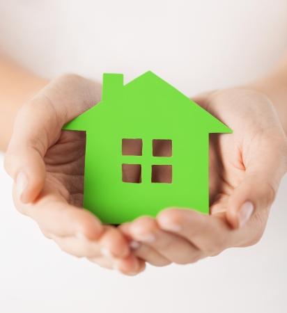 hospedaje: Foto de detalle de manos de la mujer que sostienen la casa verde