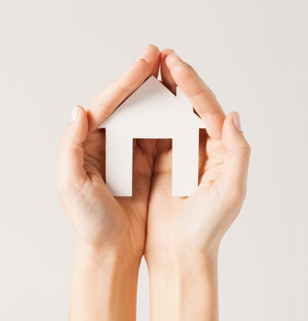 costruction: pisture of woman hands holding paper house