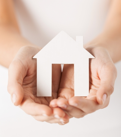 closeup pisture of woman hands holding paper house