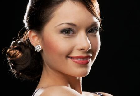 earrings: beautiful woman in evening dress wearing diamond earrings