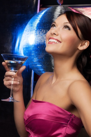 dancing club: beautiful woman in evening dress with cocktail  and disco ball