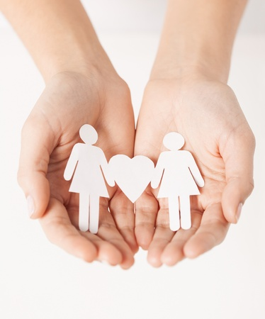 nude lesbian: womans hands showing two paper women with heart shape