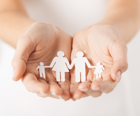 protect family: close up of womans cupped hands showing paper man family Stock Photo