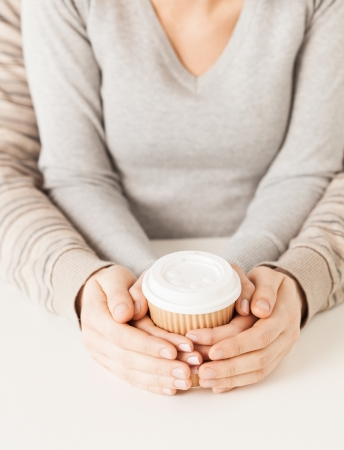 woman and man hands holding take away coffee cup photo