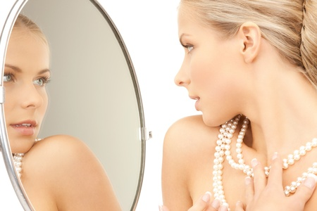 woman with pearl necklace looking in the mirror photo