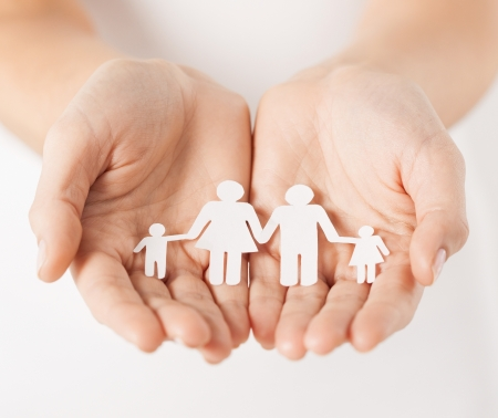 close up of womans cupped hands showing paper man family photo