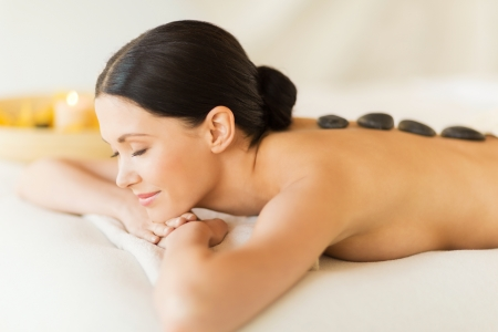 candles spa: picture of woman in spa salon with hot stones