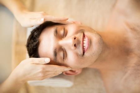 levantandose: cerca de la cara del hombre en salón del balneario que consigue masaje facial