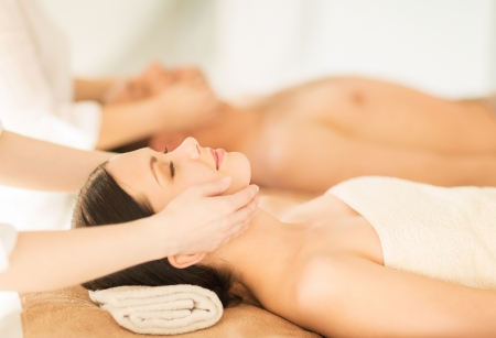 therapeutic massage: picture of couple in spa salon getting face treatment Stock Photo