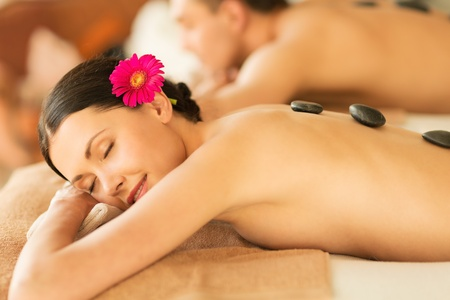 therapeutic massage: picture of couple in spa salon with hot stones