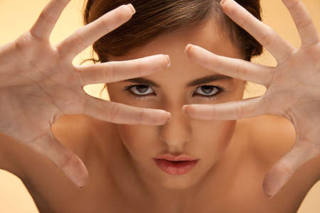 picture of futuristic woman face looking through fingers photo