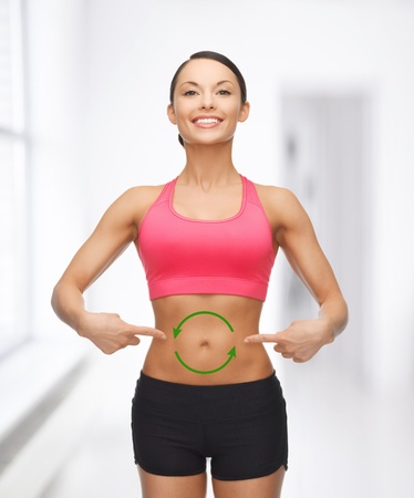 balanced diet: picture of beautiful sporty woman with arrows on her stomach Stock Photo