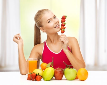 young woman with organic food or fruits eating strawberry photo