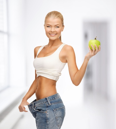 fat and slim: picture of sporty woman showing big pants and apple