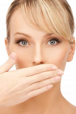 hands covering face: face of beautiful woman covering her mouth
