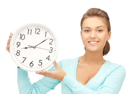 running out of time: attractive woman holding wall clock in her hands