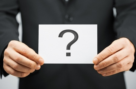 picture of man in suit holding card with question mark photo