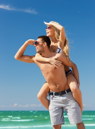 carrying girlfriend: picture of happy couple having fun on the beach