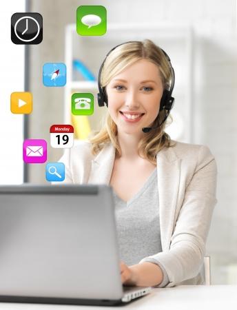 secretaries: sonriendo operador de l�nea telef�nica de ayuda femenina con auriculares y un ordenador port�til