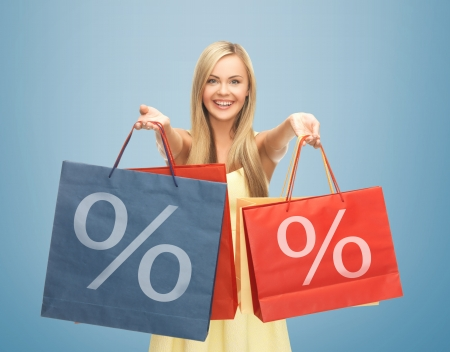 woman shopping bags: picture of happy woman holding shopping bags with percent sign