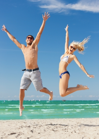picture of happy couple jumping on the beach photo