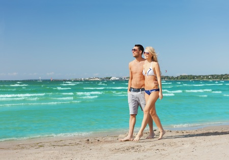 picture of happy couple walking on the beach. photo