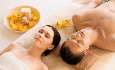 candles spa: picture of couple in spa salon lying on the massage desks