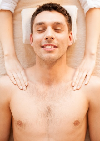 close up of man face in spa salon getting massage photo