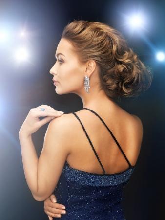traje de gala: hermosa mujer en traje de noche con aretes de diamantes