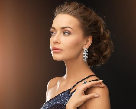 mooie vrouw in avondjurk dragen diamanten oorbellen