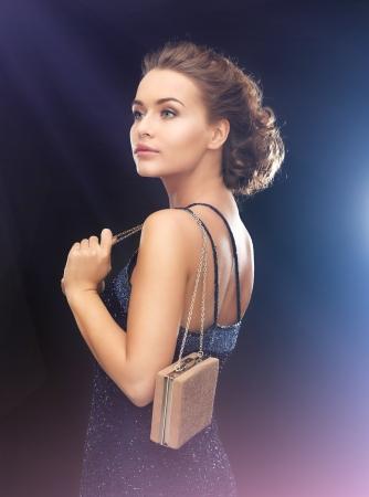 traje de gala: hermosa mujer en traje de noche con una pequeña bolsa de