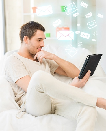 handsome man sitting on the couch with tablet pc photo