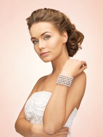 pearl background: beautiful bride wearing pearl earrings and bracelet