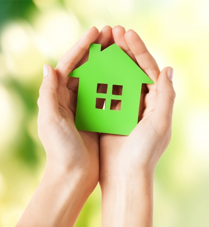 home protection: closeup picture of woman hands holding green house Stock Photo