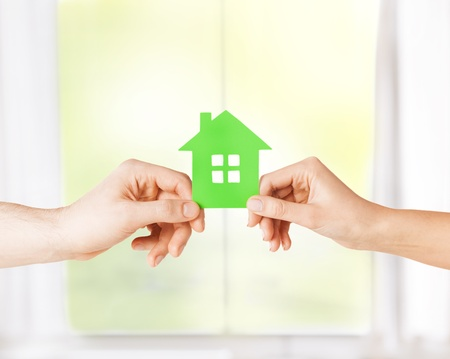 closeup picture of woman and man hands holding green house photo
